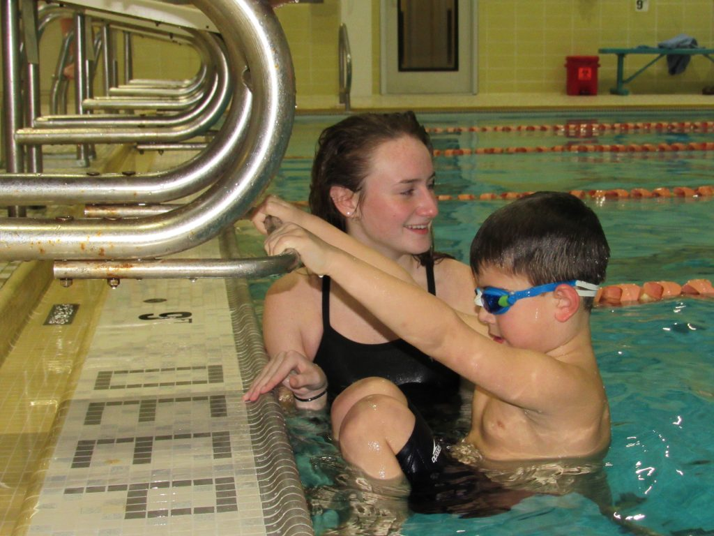 Swim Instructor helping youth swimmer